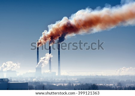 Three industrial chimney with smoke against the dark sky - stock photo