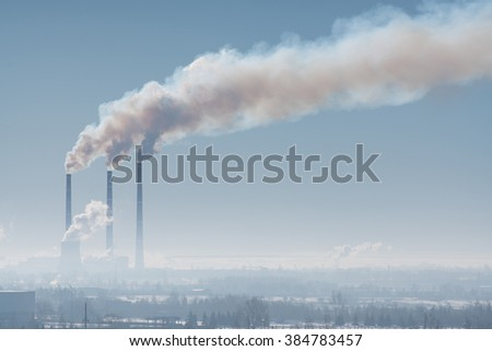 Three industrial chimney with smoke against the gray sky - stock photo