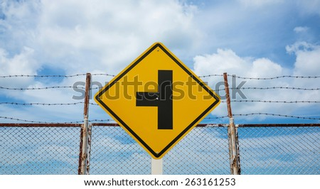 Three intersection traffic sign and Barb wire fence and blue sky - stock photo