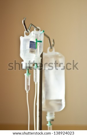 Three IV's hand on a stand in a hospital room - stock photo