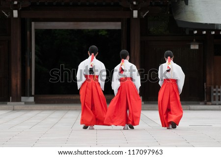 Three Japanese women in traditional outfits walk across the square of a temple in Yoyogi Park, Tokyo. - stock photo