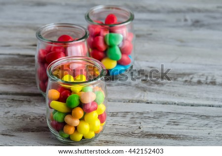 Three jars with colorful candies and sweets on wooden table - stock photo