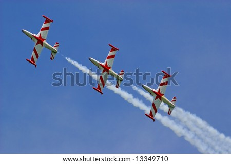 three jets in line on air show agains blue sky. - stock photo