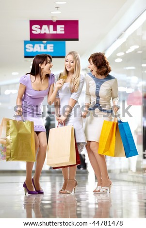 Three joyful girlfriends in shop with a credit card - stock photo