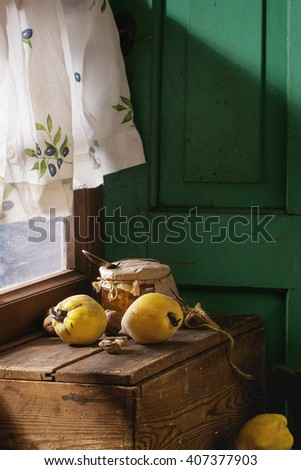Three juicy quinces, walnuts and jar of honey over wooden table near window with bright sunlight. With green wooden wall at background. Dark rustic style.  - stock photo