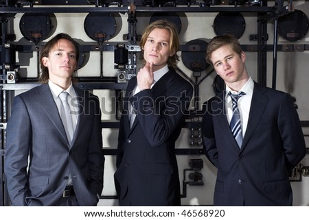 Three junior executives posing arrogantly, proud of their acquired and perceived status - stock photo