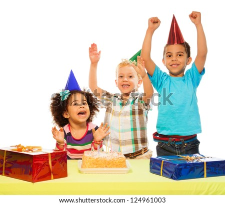 Three kids celebrating birthday - two boys and girl with cake and presents on the table - stock photo