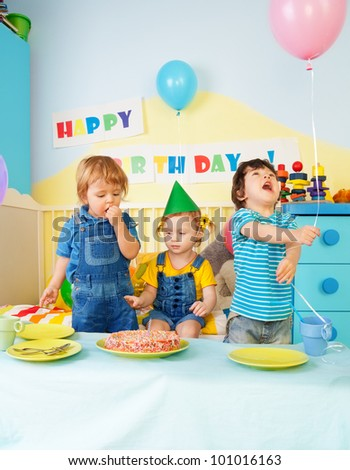 Three kids eating birthday cake at the party - stock photo