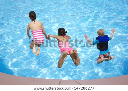 Three Kids jumping into the Swimming Pool - stock photo