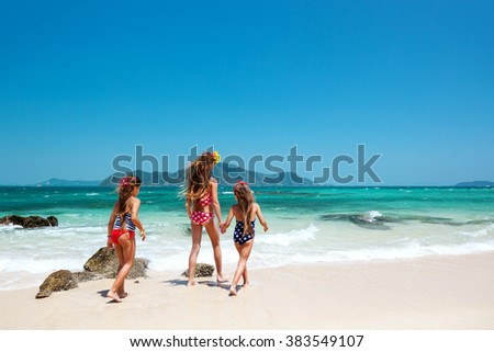 Three kids playing at the tropical beach, rear view - stock photo