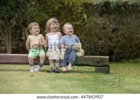 three kids seated on a beam - stock photo