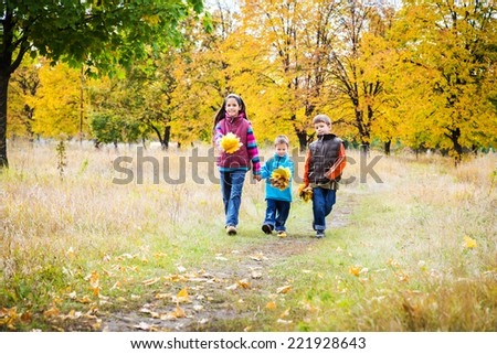Three kids walking together in autumn park - stock photo