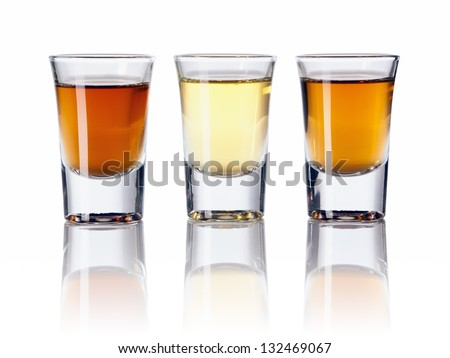 Three kinds of alcoholic drinks in shot glasses - stock photo