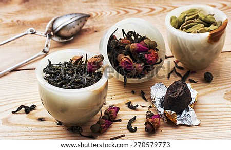 three kinds of tea infuser in tea bowl on the background of spoon for brewing beverage - stock photo