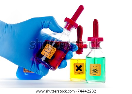 Three laboratory dropper bottles containing orange, yellow and green liquids and labelled as toxic, corrosive and irritant. One bottle is held in a blue gloved hand. On white - stock photo