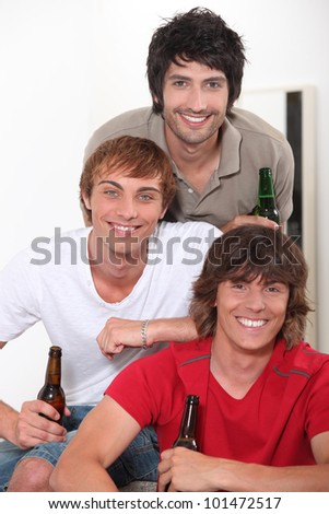 Three lads with bottles of beer - stock photo