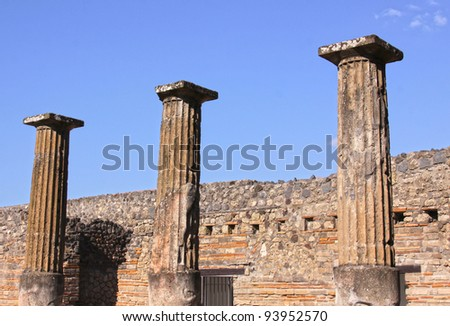 Three large preserved columns in the Roman city of Pompeii.  It was completely buried by an eruption of Mount Vesuvius in AD 79. - stock photo
