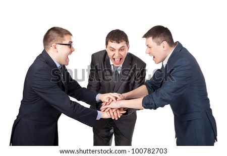 Three laughing partners putting their hands on the top isolated on white background - stock photo