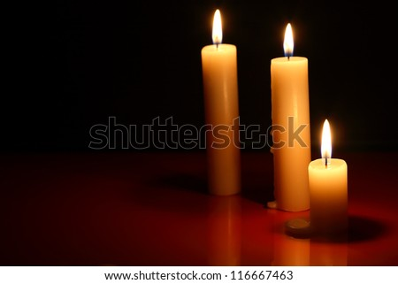 Three lighting candles on dark background with reflection - stock photo