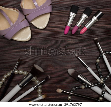 Three lipsticks set of brushes, shoes and beads on a dark wooden background - stock photo