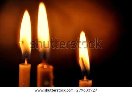 Three lit candles on a black background. - stock photo