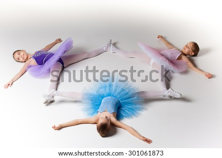 Three little ballet girls sitting in multicolored tutu together on white background - stock photo