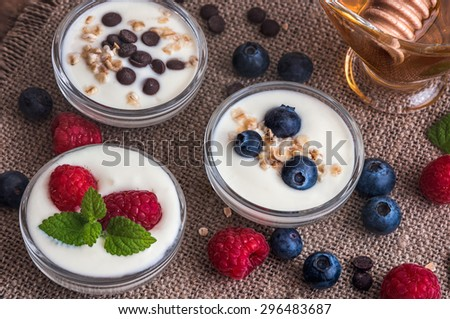 Three Little Bowls Full of Healthy Yogurt with Fruit or Chocolate and Honey on Wooden Rustic Table - stock photo