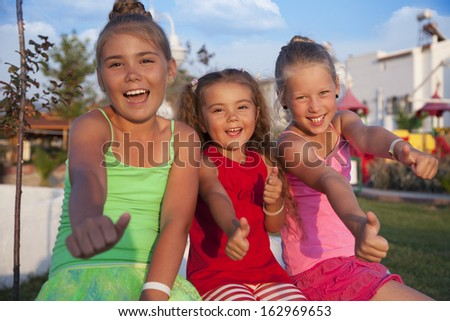 Three little Caucasian girls doing ok sign  - stock photo