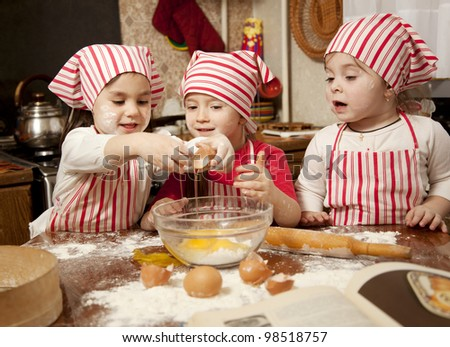 Three little chefs enjoying in the kitchen making big mess. Little girls making bread in the kitchen - stock photo