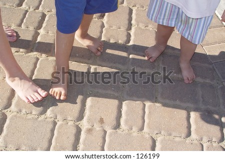 Three little children stepping on each others  shadows - stock photo