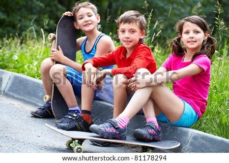 Three little children with skateboards sitting on asphalt and looking at camera - stock photo