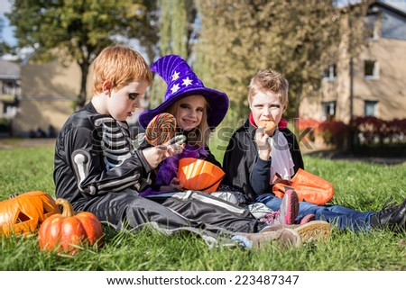 Three little cute friends sitting on the grass and eating Halloween candies. Outdoor portrait - stock photo