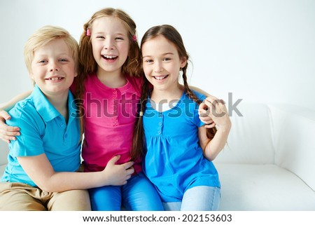 Three little friends looking at camera with smiles  - stock photo