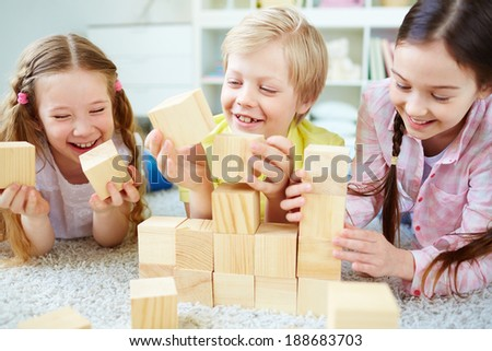 Three little friends playing with wooden bricks - stock photo