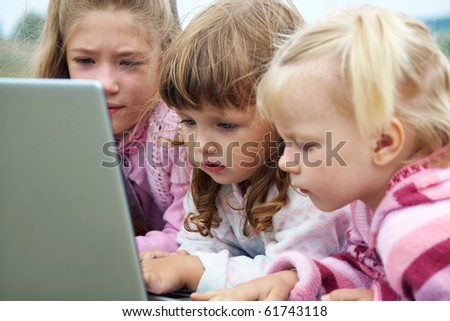three  little girls lying on the lawn and and exercise on a laptop - stock photo