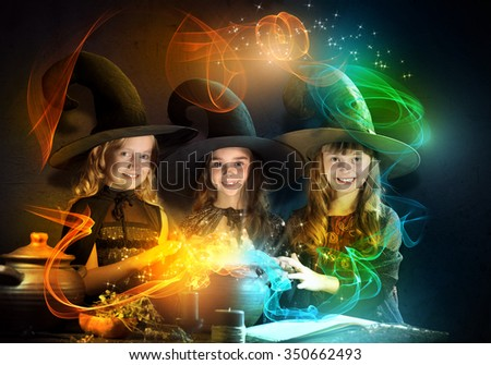 Three little Halloween witches reading conjure from magic book - stock photo