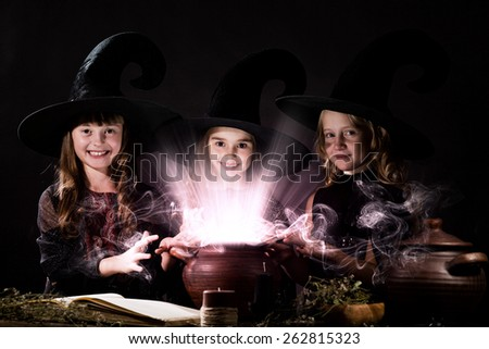 Three little Halloween witches reading spell above pot - stock photo