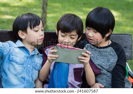 Three Little handsome boy looking on ipad tablet and playing game at park - stock photo