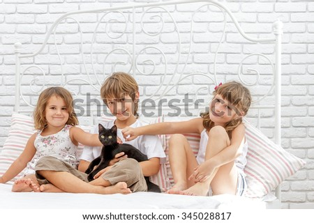 three little happy kids playing with black cat on white bed at home - stock photo