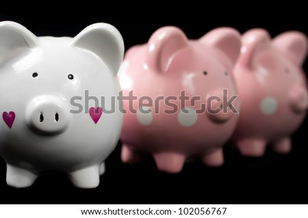 Three little piggy banks lined up. Unique white heart piggy in focus against black background - stock photo
