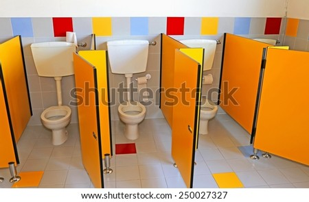 three little water closed of a kindergarten for children with yellow doors - stock photo