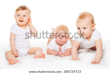 Three looking babies crawl and sit on blanket - stock photo
