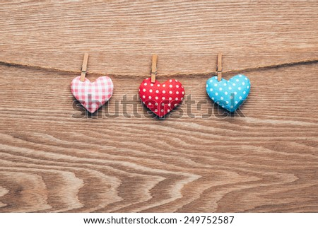 Three love hearts hanging on wooden texture background, valentines day card concept - stock photo