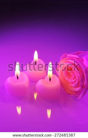 three luminous pink candlehearts with pink rose in purple light - stock photo