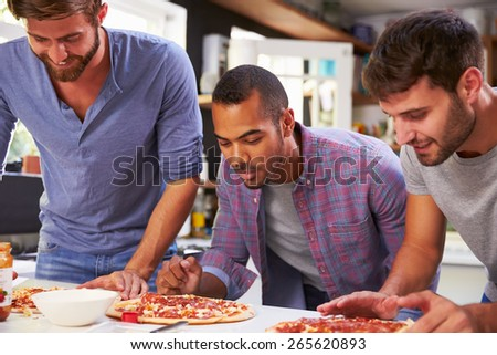 Three Male Friends Making Pizza In Kitchen Together - stock photo