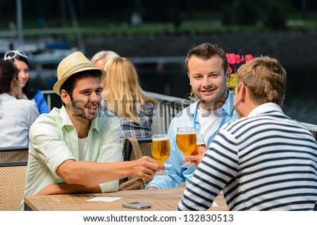 Three male friends relax drinking beer night out restaurant terrace - stock photo