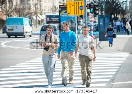 Three male friends walking down the street - stock photo