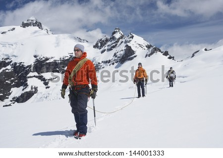 Three male hikers joined by safety line on snowy mountains - stock photo