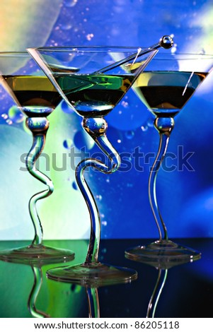 Three martinis in glasses with curved stems in front of colorful lighted background - stock photo