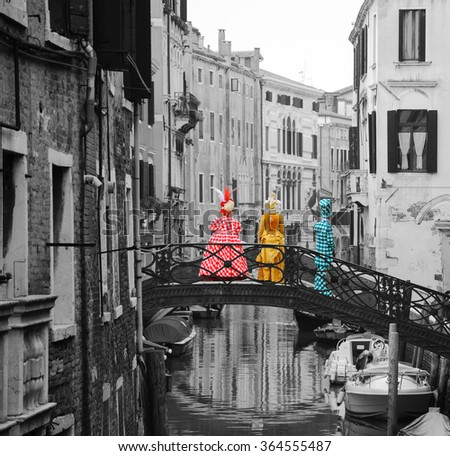 Three masks in checkered colorful costumes standing on the bridge over canal. Back view. Carnival in Venice (Italy). Toned black and white photo. - stock photo